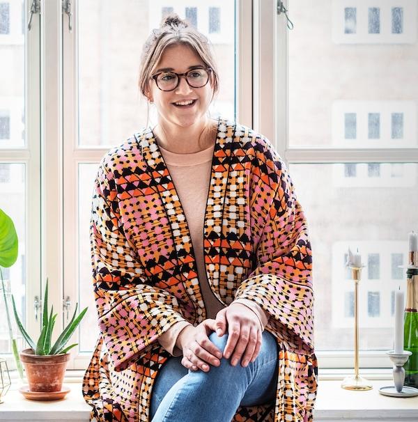 Glimlachende jonge vrouw draagt een kleurrijke kaftan en zit op de vensterbank van haar flat.