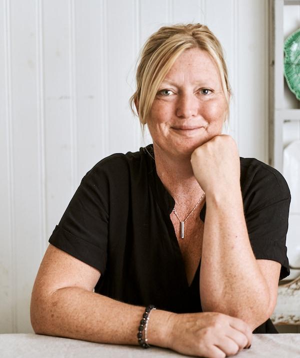 Glimlachende vrouw met blond haar en een zwart T-shirt zit aan een eettafel in een kamer met witte houten wandpanelen.
