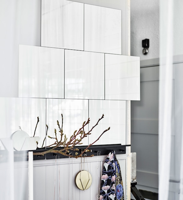 Glossy white tiles mounted onto a white wall and reflecting natural light to brighten up the airy bedroom.