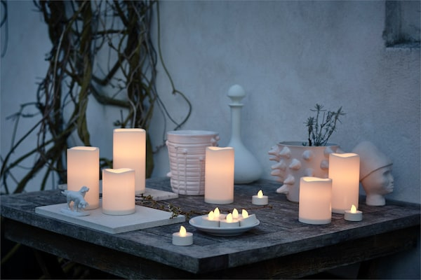 GODAFTON LED block candles sit on on outdoor table with decorative accessories.