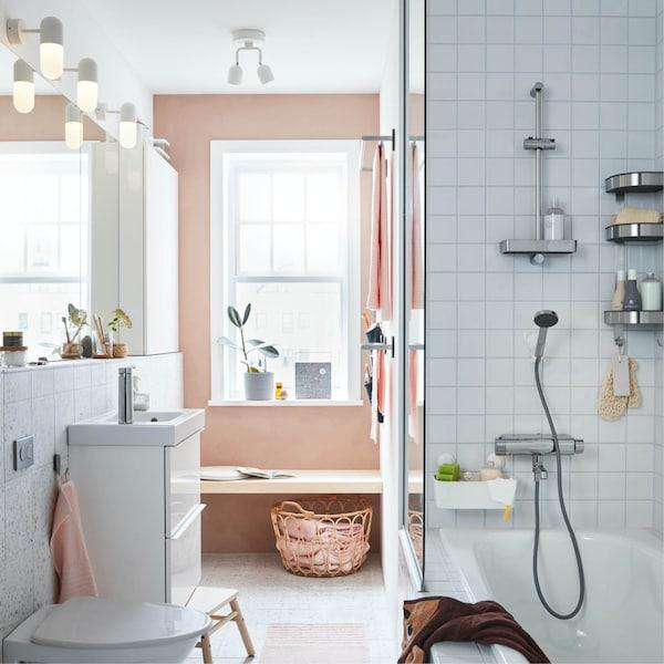 GODMORGON / BRÅVIKEN kast met wastafel in een witte betegelde badkamer met zicht op een roze muur met venster