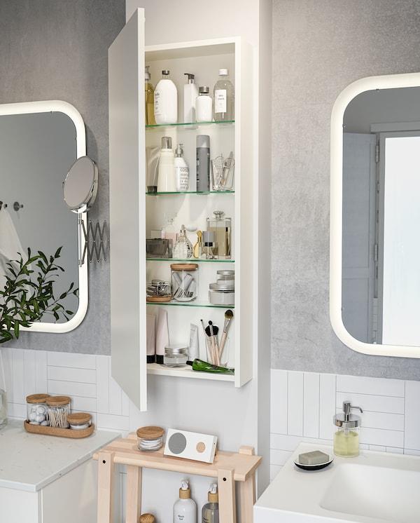 GODMORGON خزانة مرتفعة مثبتة بالحائط بين اثنين من مرايا الحمامات. الباب مفتوح، والمنتجات فوق الرفوف.