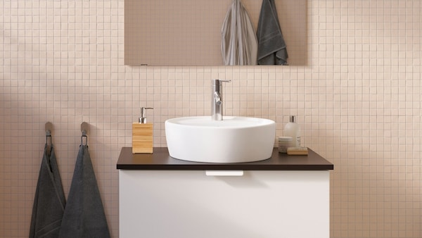 GODMORGON-sarjan allaskaappi jossa on tumma taso ja valkoiset vetolaatikot. Tason keskellä on pyöreä pesuallas