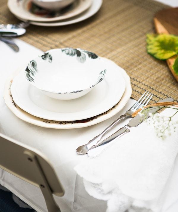 Gomila posuđa i pribora za jelo na nadstolnjaku od morske trave i bijelom stolnjaku.