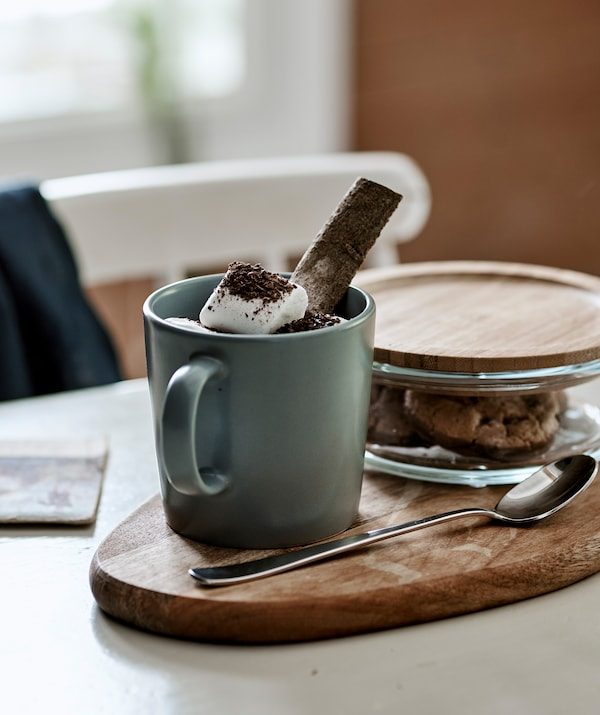 Горячий шоколад с маршмеллоу в серо-голубой чашке, стоящей на разделочной доске; в стеклянной банке с бамбуковой крышкой лежит печенье.