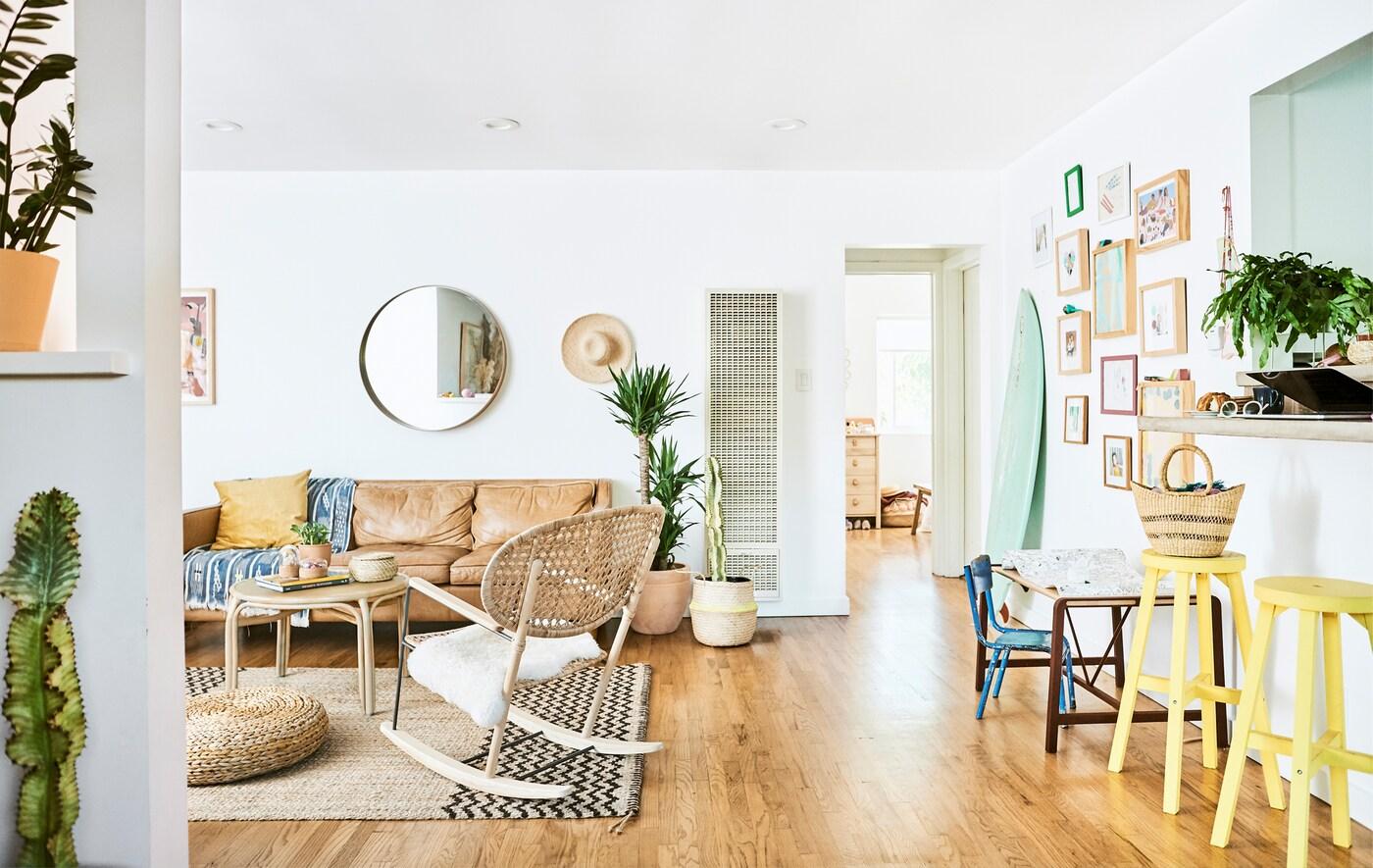 Гостиная с кожаным диваном, ротанговым креслом-качалкой, гессенским ковром, деревянным полом и двумя желтыми табуретками вдоль стойки.