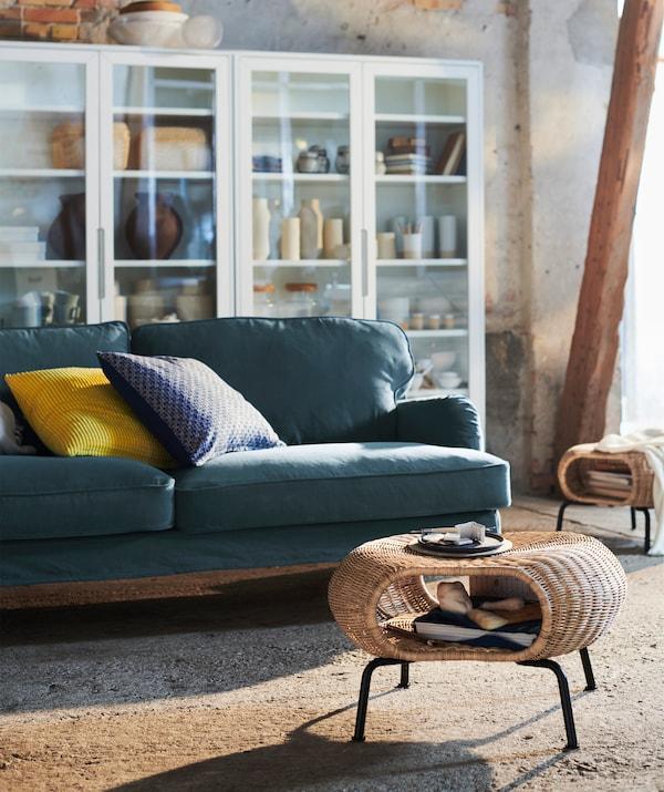 Гостиная с табуретом из ротанга и металла, темно-зеленым диваном и напольными шкафами со стеклянным фасадом.