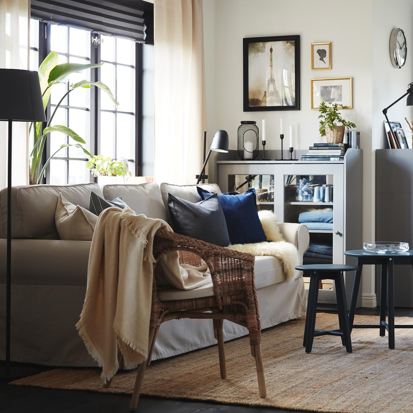 Гостиная со светло-бежевым диваном-кроватью, ковер из джута, стул из ротанга и бамбука, два шкафа и серый комод.