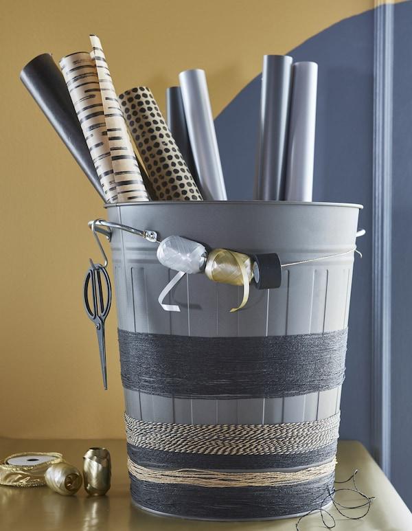 Grå KNODD spand med gavepapir, snor viklet om spanden og ruller med gavebånd.