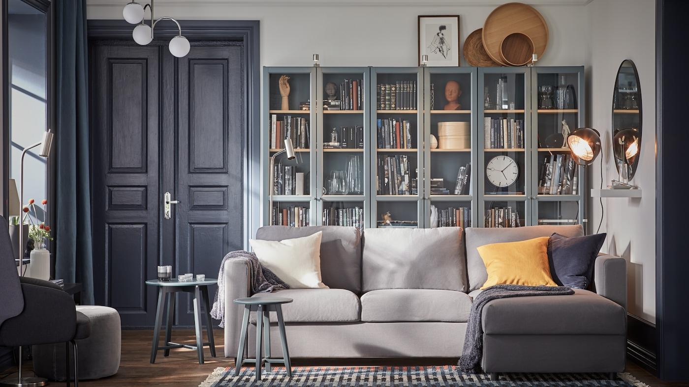Grå sofa med sjeselong og tre grå turkise bokhyller med vitrinedører og mange bøker.