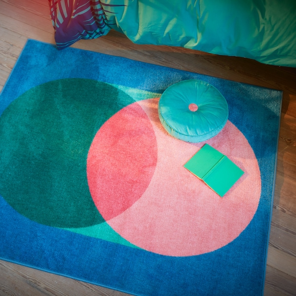 GRACIÖS rug with a big circular pattern in pink and green on a blue background, with a book and cushion  placed on it.