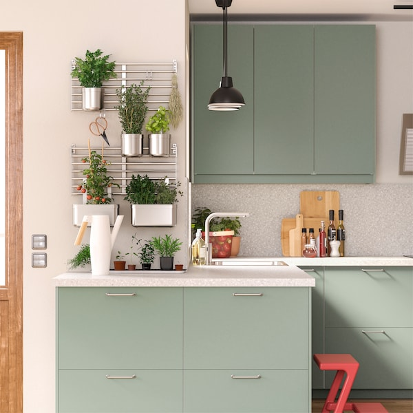Grågrønt køkken med vægmonterede væggitre af rustfrit stål, hvor der hænger urtepotteskjulere med forskellige krydderurter og grøntsager.