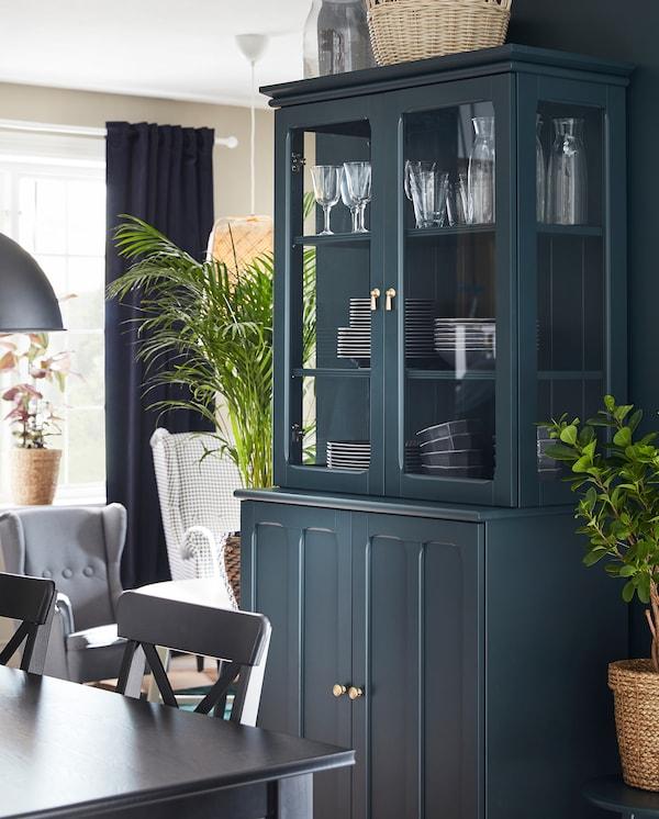 Granatowo-zielona szafka LOMMARP ze szklanymi drzwiami stoi obok stołu jadalnianego, za szklanymi drzwiami widać zastawę stołową.