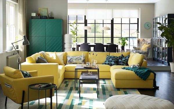 Grand canapé jaune en U au centre d'un salon-salle à manger.