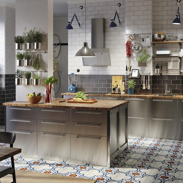Grande cuisine avec façades en acier inoxydable, plans de travail en chêne/placage, lampes de travail industrielles bleues et herbes aromatiques en pots.