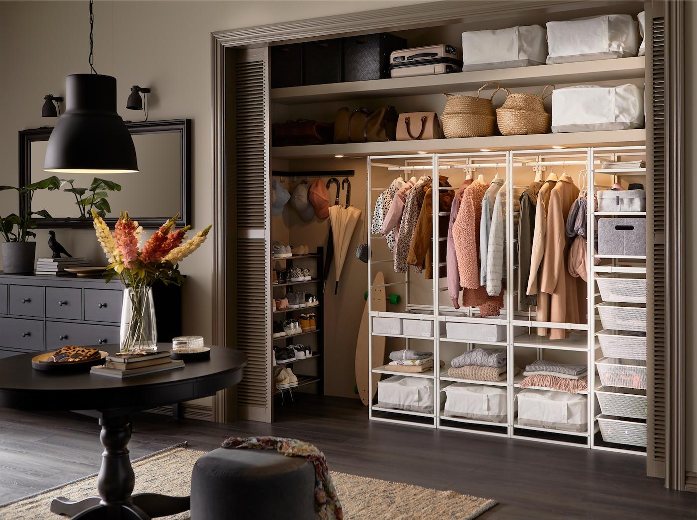 Grande entrée avec garde-robe intégrée et système de rangement JONAXEL en blanc, boîtes à compartiments blanches et éclairage intégré.