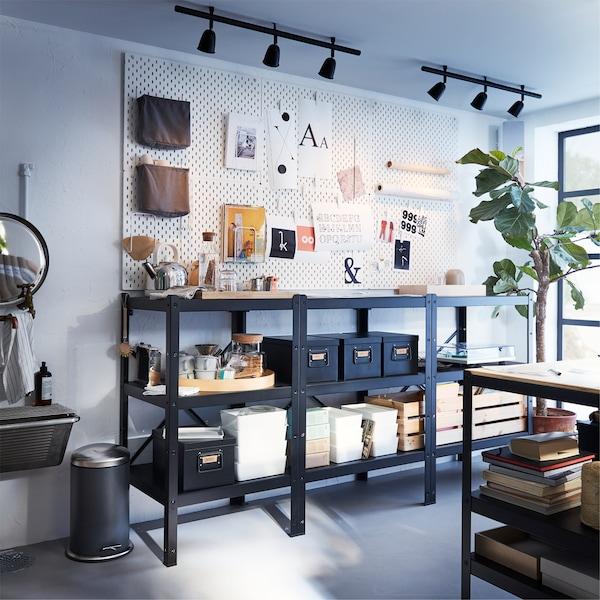 Grande étagère noire. Au-dessus, des panneaux perforés blancs avec différents accessoires et des spots sur deux rails noirs.