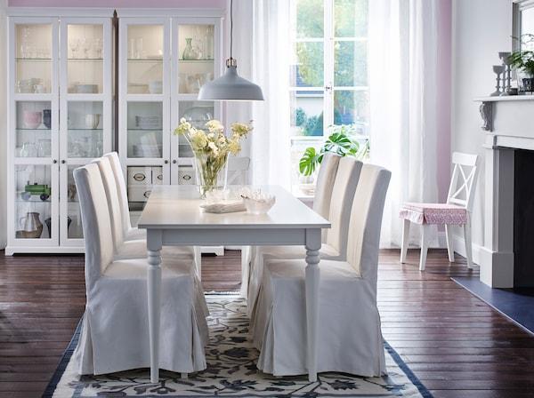 Grande salle à manger avec table à manger blanc et six chaises recouvertes d'une housse de coton blanc. Contre le mur deux grandes vitrines blanches.