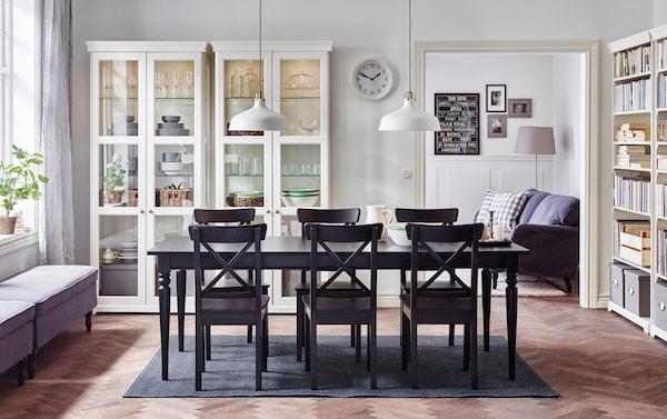 Grande salle à manger avec table à manger noire extensible et chaises et contre le mur deux vitrines blanches.