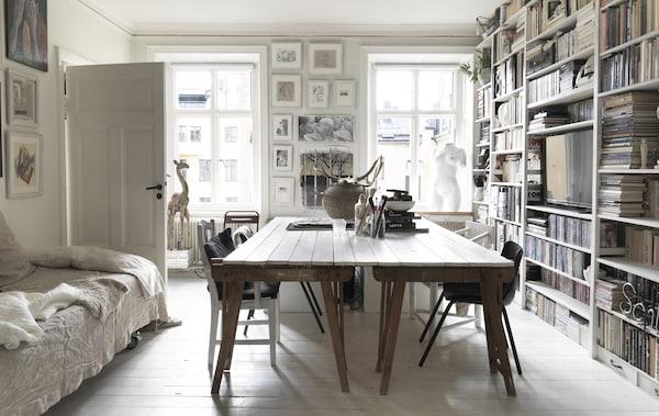 Grande table de salle à manger et mur de bibliothèques.
