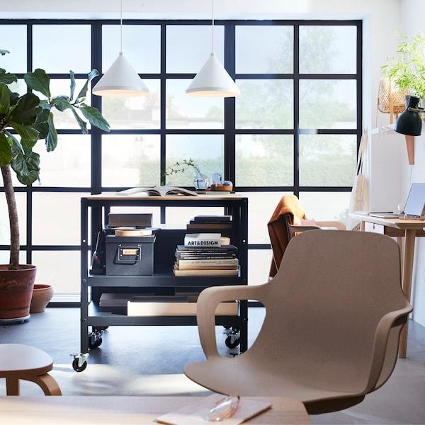 Grandes fenêtres au cadre noir, deux suspensions blanches, une chaise pivotante beige et une desserte en pin et noir.