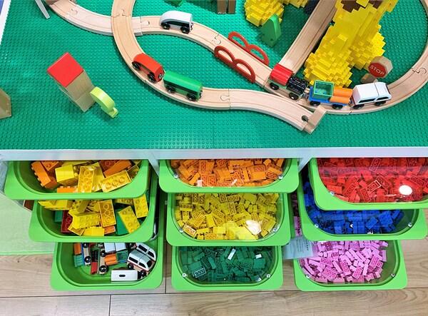 Grands bacs verts contenant des blocs de construction et insérés dans un module de rangement.