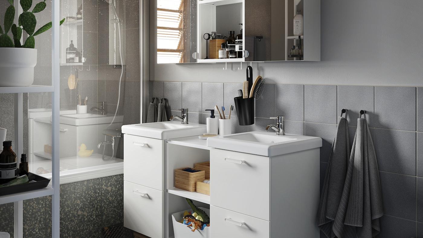 Gråt badeværelse med skab med vask i hvid, skab med spejllåger og grå badehåndklæder og bademåtte.