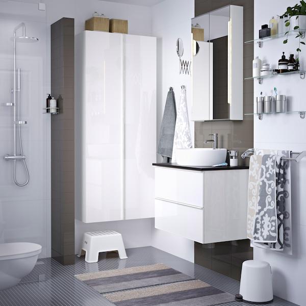 Grått och vitt badrum med vit kommod och skåp.