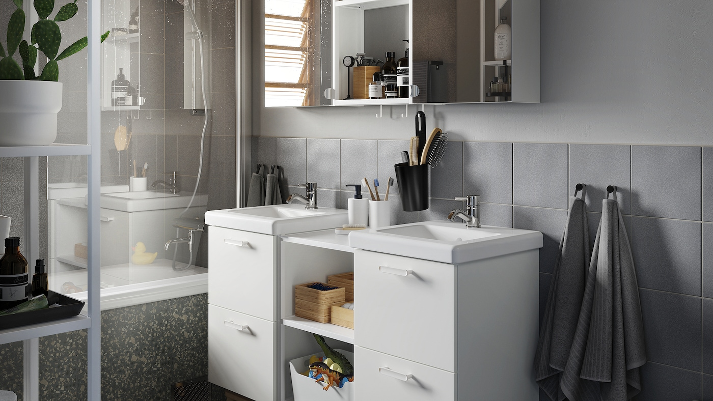 Graues Badezimmer mit Waschkommode/Waschbecken in der Mitte, einem Schrank mit Spiegeltüren sowie Handtüchern in Grau.