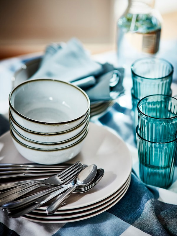 Gray GLADELIG bowls stacked on dinner plates with cutlery and KALLNA green glasses on the side