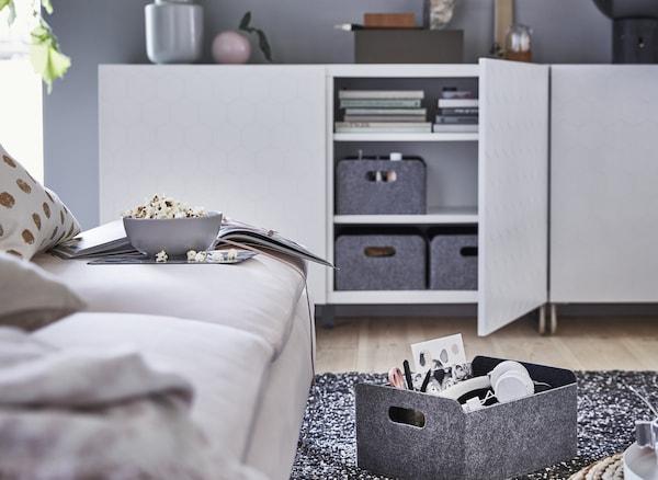 Gray storage boxes inside a low white storage unit.