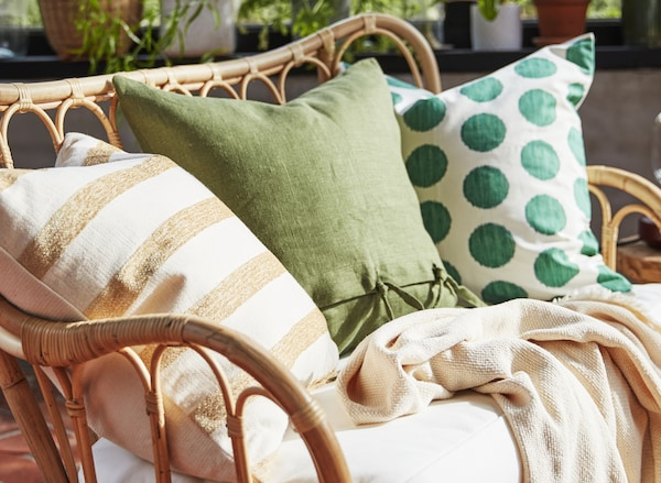 Green and yellow cushions on a rattan outdoor sofa