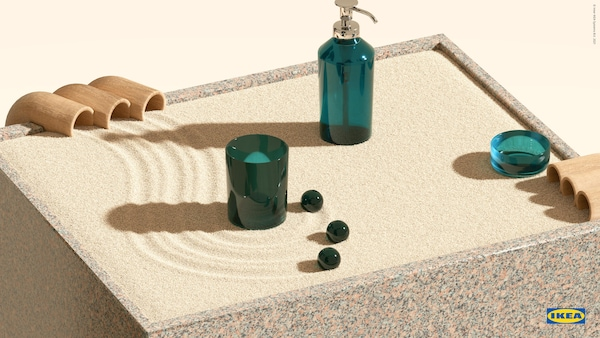 Green-glass SKISSEN soap dispenser, toothbrush holder and tray on a podium of swirled sand, against a yellow background.