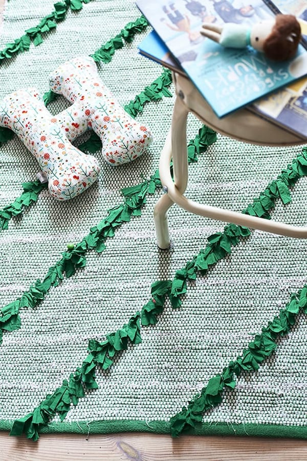 green rug with cream stool