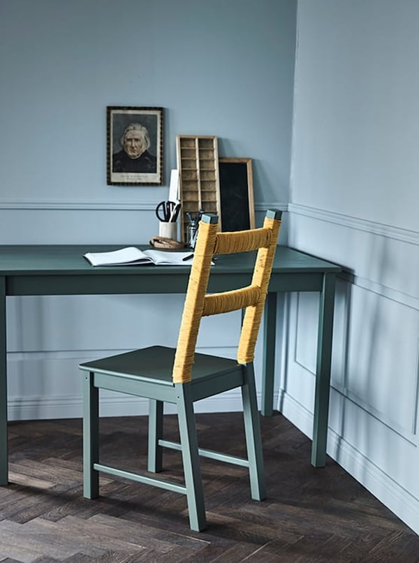 Green seat with twine around the backrest at a green desk
