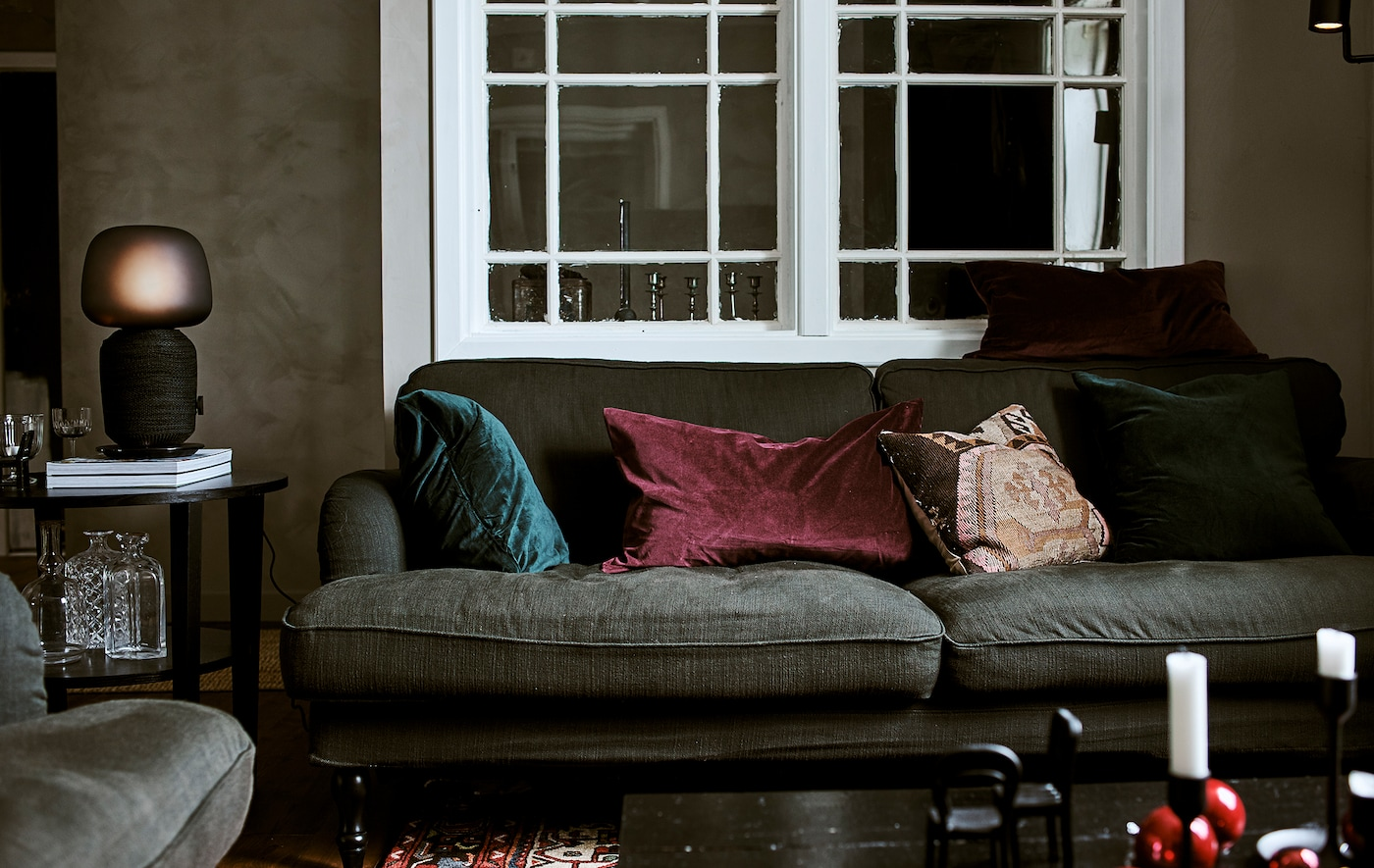 Green sofa with jewel-colored cushions in a living room with interior window, coffee table with table lamp and Persian rug.