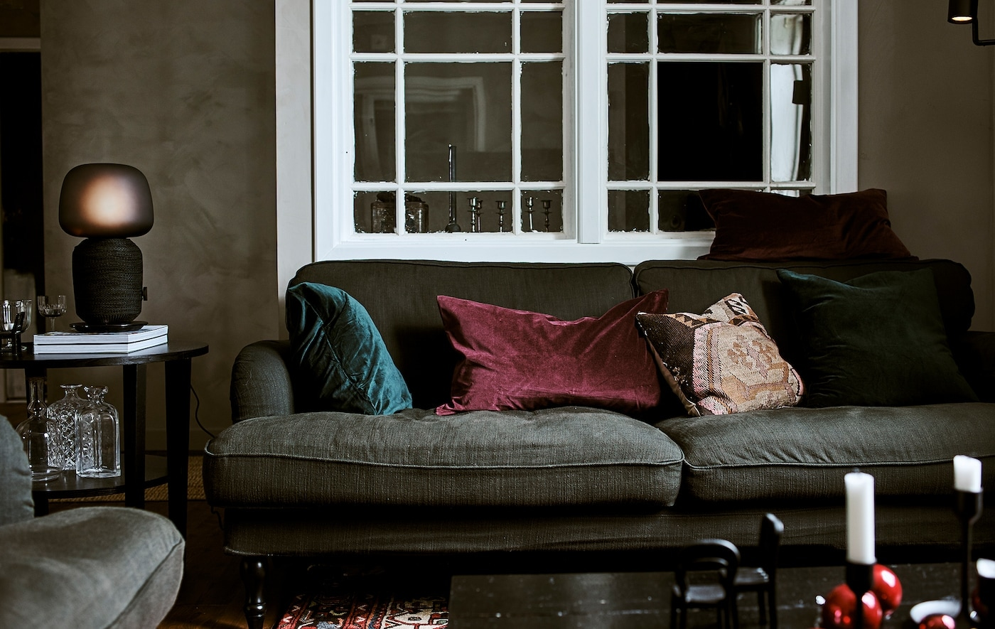 Green sofa with jewel-coloured cushions in a living room with interior window, coffee table with table lamp and Persian rug.