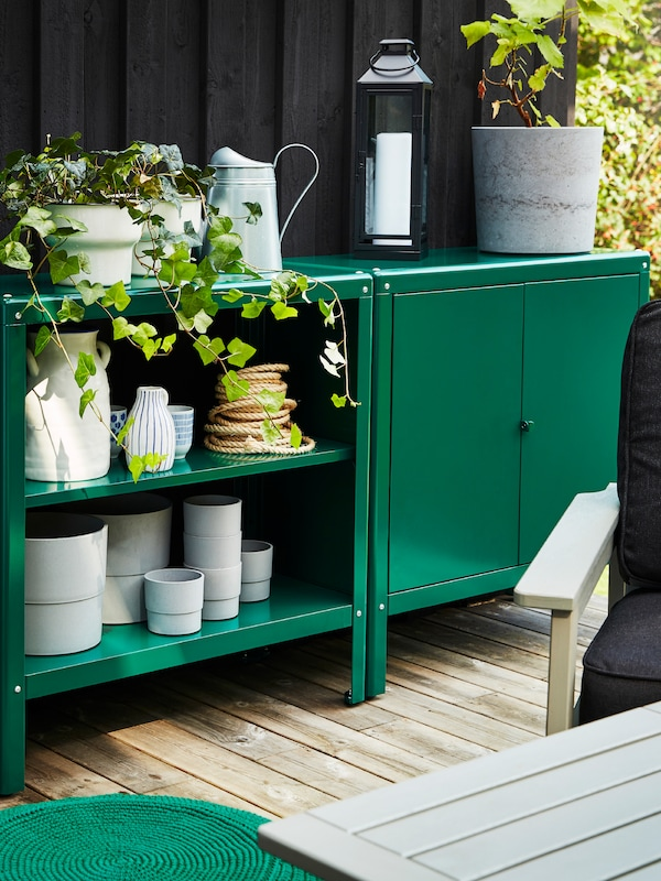 Green storage units outside, holding various pots, jugs and plants in plant pots, a lantern and some table mats.