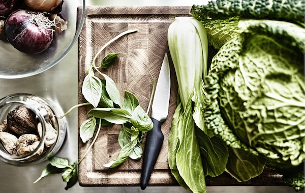 Green vegetables and leaves on a wooden chopping board.