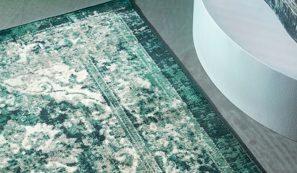 Green VONSBÄK rug with vintage, worn-in look against a grey-green floor.