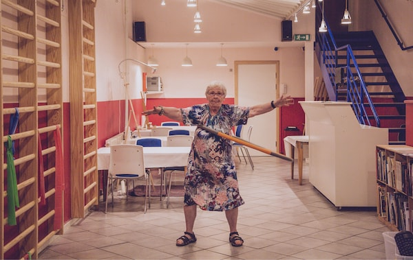 Greta dances with a hula hoop in a dining room with red and white walls.
