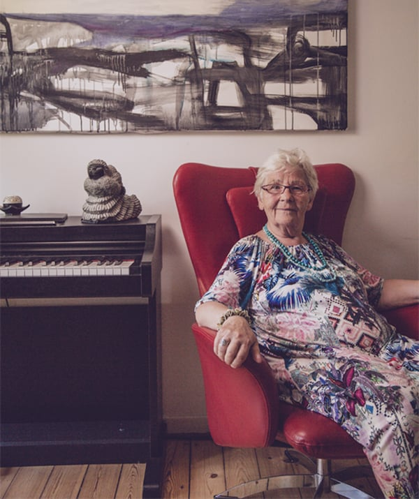 Greta sits in a red winged chair next to a piano with artwork on the wall behind her.