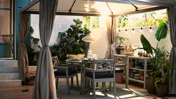 Grey BONDHOLMEN outdoor dining table and chairs for four people to enjoy dinner outside on the deck under a fabric gazebo.