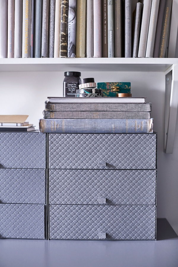 Grey boxes with drawers sit on a desk in a dorm room.