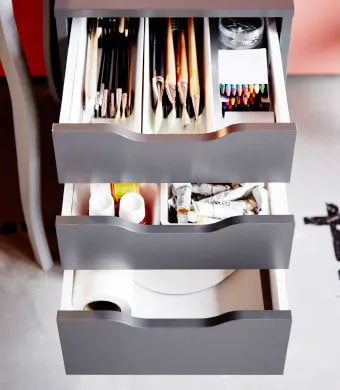 Grey drawer unit with the three drawers open and filled with art supplies