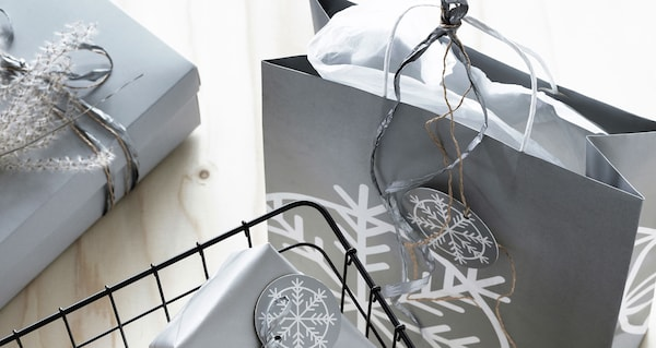 Grey holiday gift bags with silver ribbon and snowflake gift tags on a wooden table