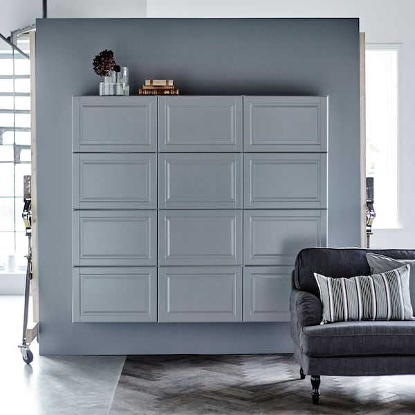 Grey METOD cabinets against a grey wall with a sofa in front.