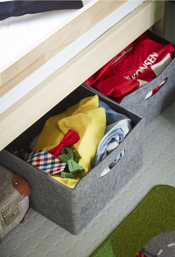 Grey storage boxes under a bed.