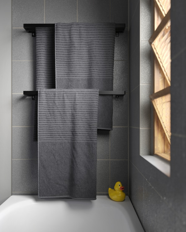 Grey towels hang on two black towels rails that are wall-mounted over a bathtub. A rubber duck stands in the bathtub corner.