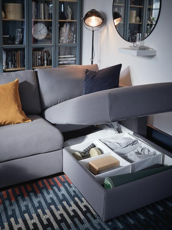 Grijze chaise longue die geopend is en met een aantal kussens op een veelkleurig tapijt en in de opbergruimte allerlei spulletjes.